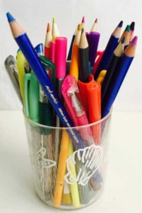 Cup containing various coloring media eg pens, markers, gel pens, and watercolor pencils.